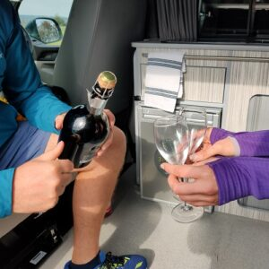 Celebrating with champagne in a Breakout Campers campervan